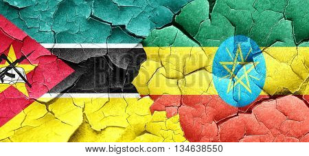 Mozambique flag with Ethiopia flag on a grunge cracked wall