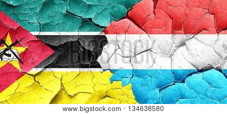Mozambique flag with Luxembourg flag on a grunge cracked wall