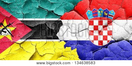 Mozambique flag with Croatia flag on a grunge cracked wall