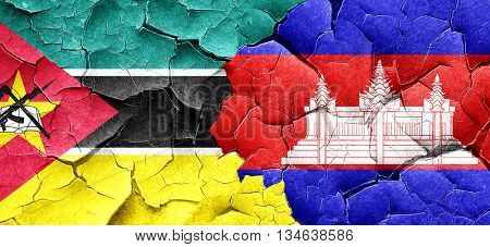 Mozambique flag with Cambodia flag on a grunge cracked wall