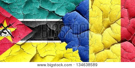 Mozambique flag with Romania flag on a grunge cracked wall