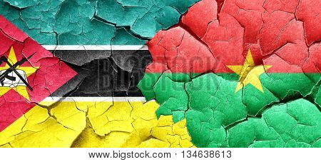 Mozambique flag with Burkina Faso flag on a grunge cracked wall