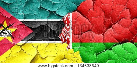 Mozambique flag with Belarus flag on a grunge cracked wall
