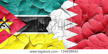 Mozambique flag with Bahrain flag on a grunge cracked wall