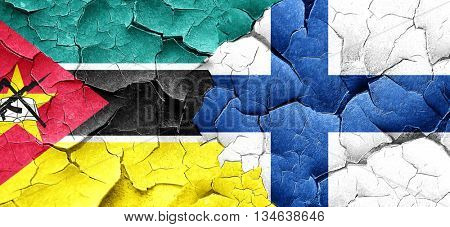 Mozambique flag with Finland flag on a grunge cracked wall