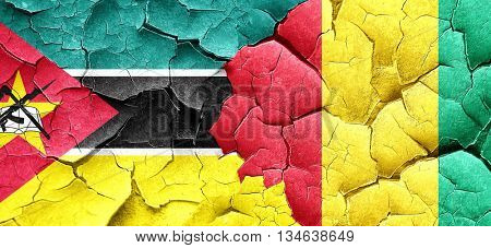 Mozambique flag with Guinea flag on a grunge cracked wall