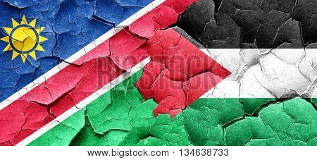 Namibia flag with Palestine flag on a grunge cracked wall