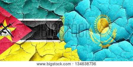 Mozambique flag with Kazakhstan flag on a grunge cracked wall