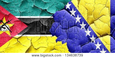 Mozambique flag with Bosnia and Herzegovina flag on a grunge cra