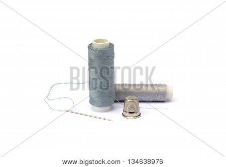 Needle, thimble, scissors, thread isolated on white background