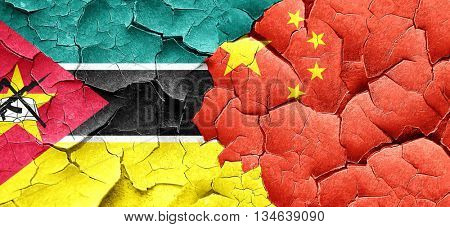 Mozambique flag with China flag on a grunge cracked wall