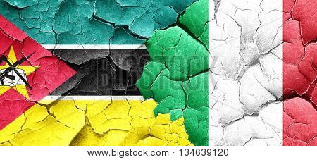 Mozambique flag with Italy flag on a grunge cracked wall