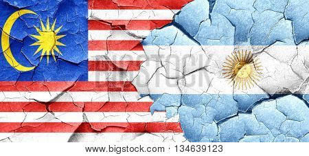 Malaysia flag with Argentine flag on a grunge cracked wall
