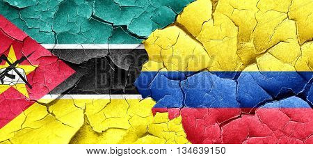 Mozambique flag with Colombia flag on a grunge cracked wall