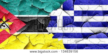 Mozambique flag with Greece flag on a grunge cracked wall