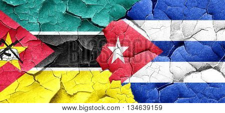 Mozambique flag with cuba flag on a grunge cracked wall