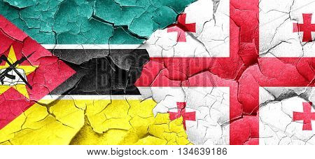 Mozambique flag with Georgia flag on a grunge cracked wall