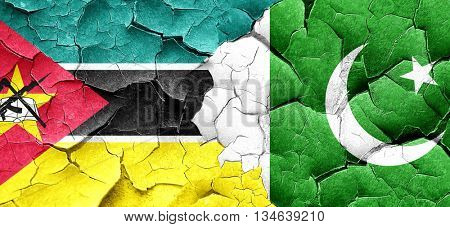 Mozambique flag with Pakistan flag on a grunge cracked wall
