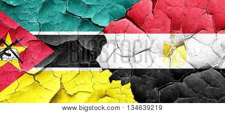 Mozambique flag with egypt flag on a grunge cracked wall