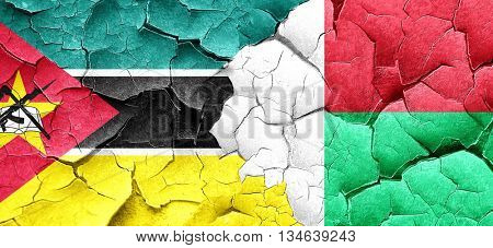 Mozambique flag with Madagascar flag on a grunge cracked wall