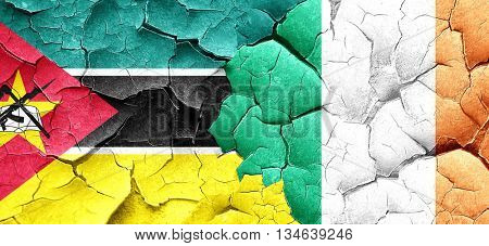 Mozambique flag with Ireland flag on a grunge cracked wall