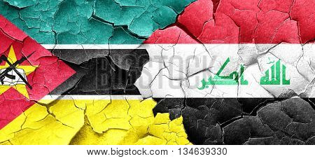 Mozambique flag with Iraq flag on a grunge cracked wall