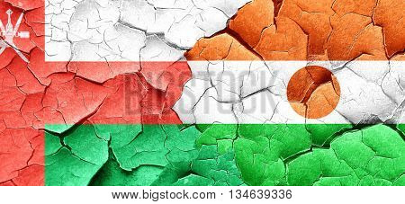 Oman flag with Niger flag on a grunge cracked wall