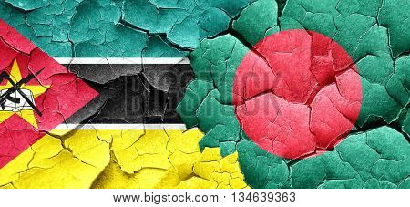 Mozambique flag with Bangladesh flag on a grunge cracked wall