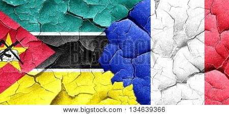 Mozambique flag with France flag on a grunge cracked wall