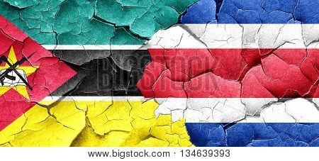 Mozambique flag with Costa Rica flag on a grunge cracked wall