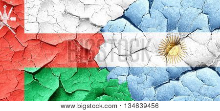 Oman flag with Argentine flag on a grunge cracked wall