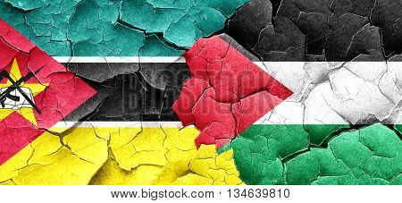 Mozambique flag with Palestine flag on a grunge cracked wall