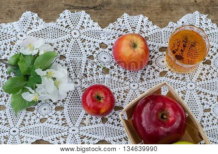 Red and tasty apples with a glass of cider (apple juice) on wooden background