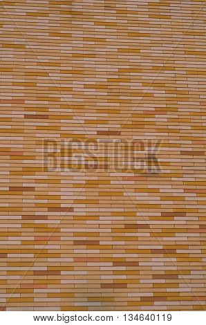 Yellow tile siding of a building. Abstract pattern of yellow and orange bricks.