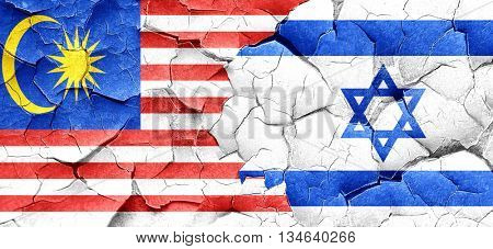 Malaysia flag with Israel flag on a grunge cracked wall
