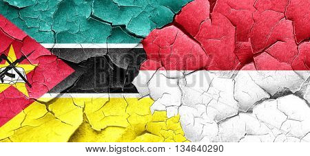 Mozambique flag with Indonesia flag on a grunge cracked wall