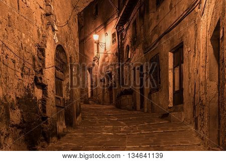 Street of ancient medieval tuff city Sorano at night  - travel european background