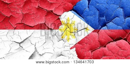 monaco flag with Philippines flag on a grunge cracked wall