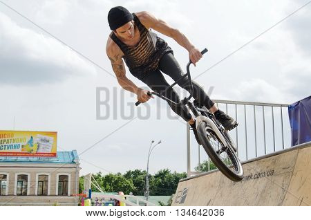KHARKOV UKRAINE - JUNE 12 2016: Young boy is showing extreme jumps on a skate stage