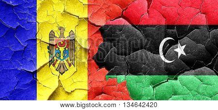 Moldova flag with Libya flag on a grunge cracked wall