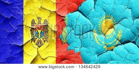 Moldova flag with Kazakhstan flag on a grunge cracked wall