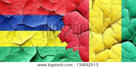 Mauritius flag with Guinea flag on a grunge cracked wall