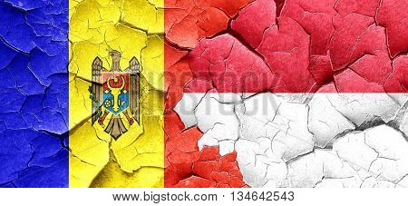 Moldova flag with Indonesia flag on a grunge cracked wall