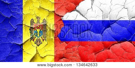 Moldova flag with Russia flag on a grunge cracked wall