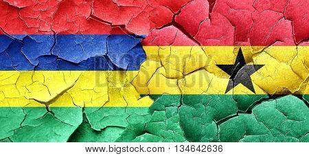 Mauritius flag with Ghana flag on a grunge cracked wall