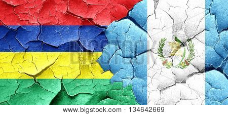 Mauritius flag with Guatemala flag on a grunge cracked wall