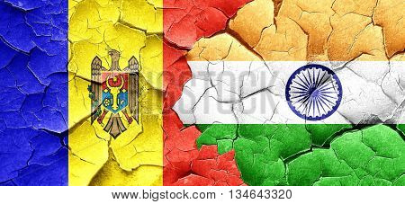 Moldova flag with India flag on a grunge cracked wall
