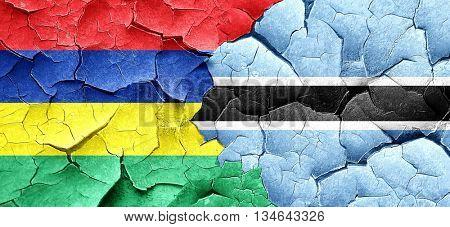 Mauritius flag with Botswana flag on a grunge cracked wall
