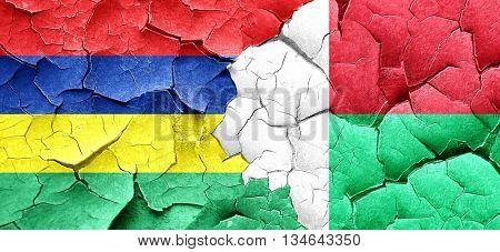 Mauritius flag with Madagascar flag on a grunge cracked wall