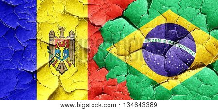 Moldova flag with Brazil flag on a grunge cracked wall